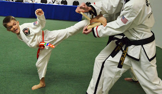 Martial arts kid breaking board with side kick