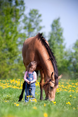 Niña con su mascota que es un caballo en el campo
