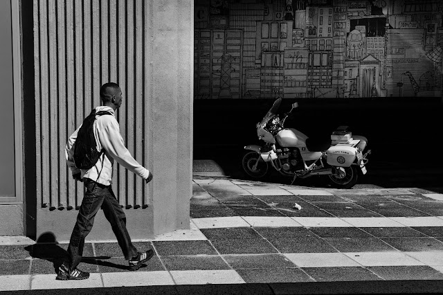 A man walk past a police motorcycle.