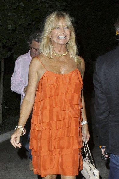 Goldie Hawn Goldie Hawn and Kurt Russell leave Bouchon restaurant in good spirits with friends, stopping for a photograph outside. Goldie was looking vibrant in an orange layered dress and sandals.