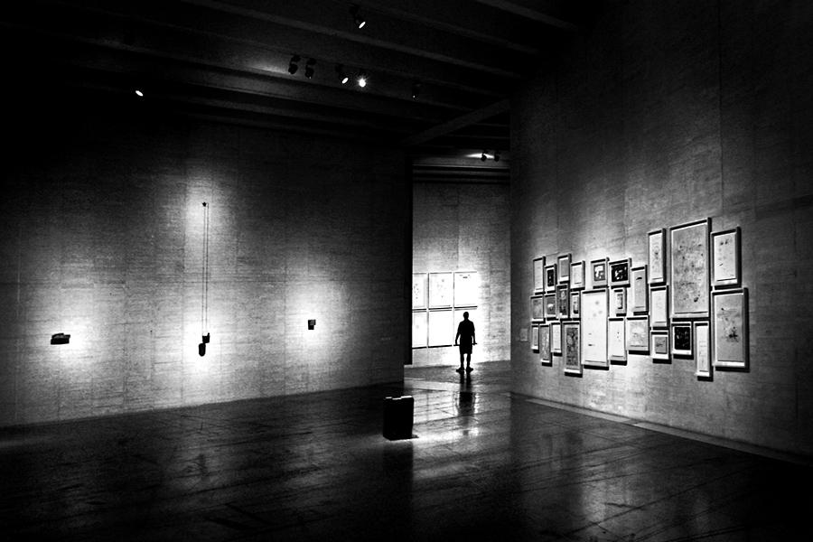Sala de exposições com o pé direito muito alto. Na parede da esquerda, objectos fortemente iluminados, na da direita quadros pequenos muito aglomerados e em frente, um homem na passagem para outra sala