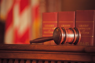 Picture of a gavel on law books in court.