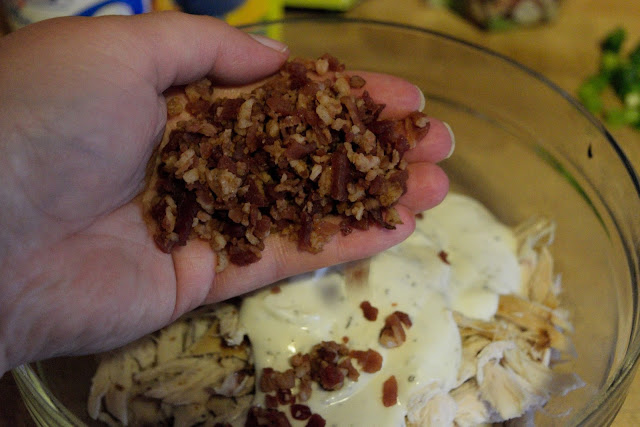 A picture of the shredded chicken and ranch in a bowl, with a palm full of bacon bits being poured into it.