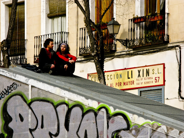 A couple having a conversation sitting on top of a big, slanted screen in Madrid, Spain.
