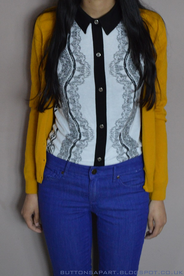 An outfit picture of a printed top, mustard cardigan and cobalt blue jeans
