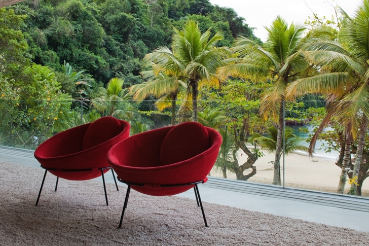 Red chairs in Modern beach house in Brazil by Marcio Kogan