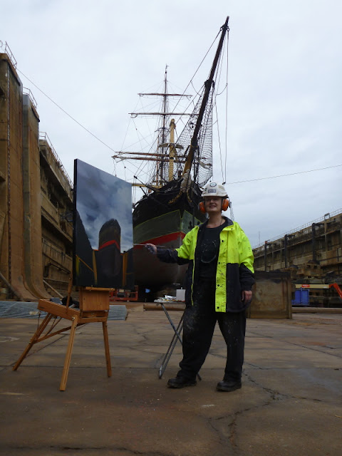 "Artist Jane Bennett with her unfinished plein air painting of  ""Painters with 'James Craig ' in Garden Island dry dock"""