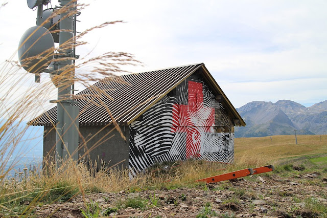 Andrew Antonaccio & Filio Orlan from 2alas just finished their piece for the great Vision Art Festival that is now happening in Crans-Montana in Swiss Alps. The duo picked a lonely hut on the cliff and painted their vision of a Swiss mountain shelter.