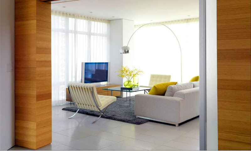 Modern living room with lots of mid-century modern pieces (Barcelona leather chairs and Arco floor lamp),  a boxy sofa,  monochromatic grey rug, yellow accent pillows and large floor length windows covered with sheer curtains