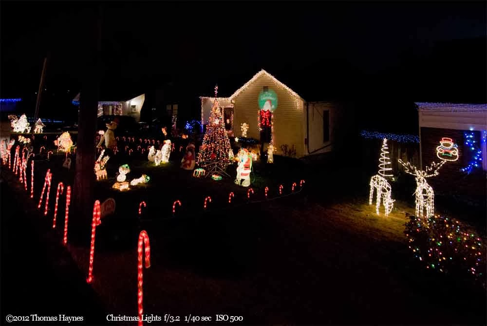 House with christmas lights adorning home and yard