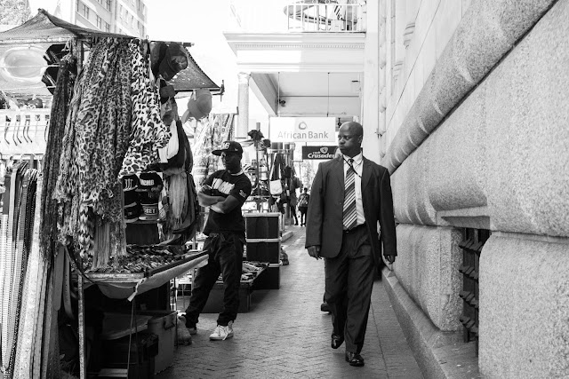A business man walks down a street in Cape Town while a street vendor looks on.