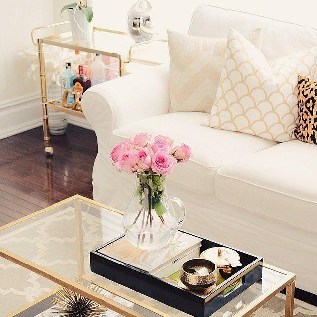 Sofá branco, carrinho dourado, almofadas branco e amarelo