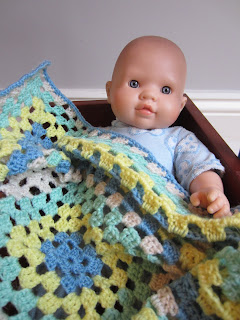 Doll in bed with granny blanket