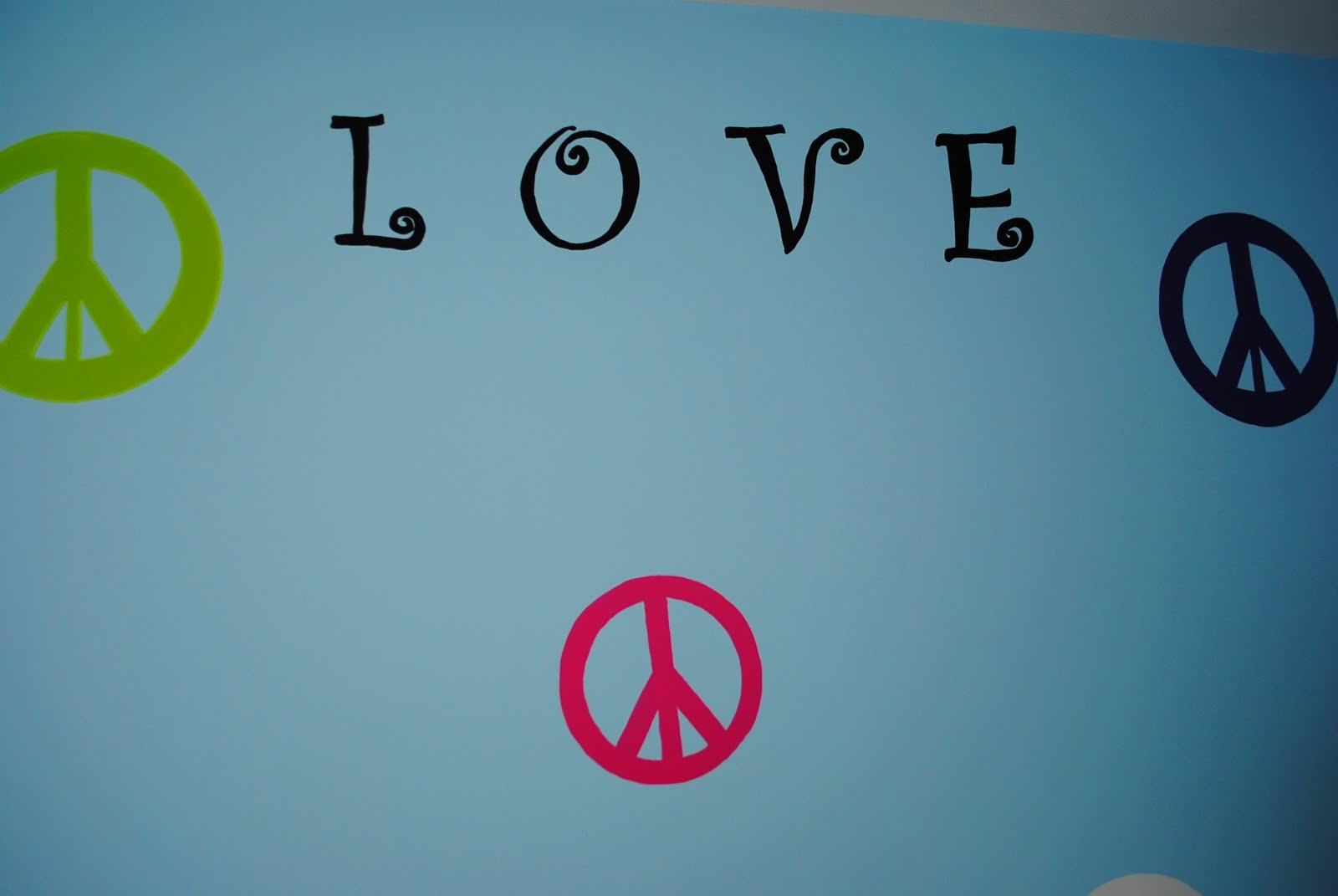 We painted the peace signs in with green, purple, pink & white, while the words were done in black.