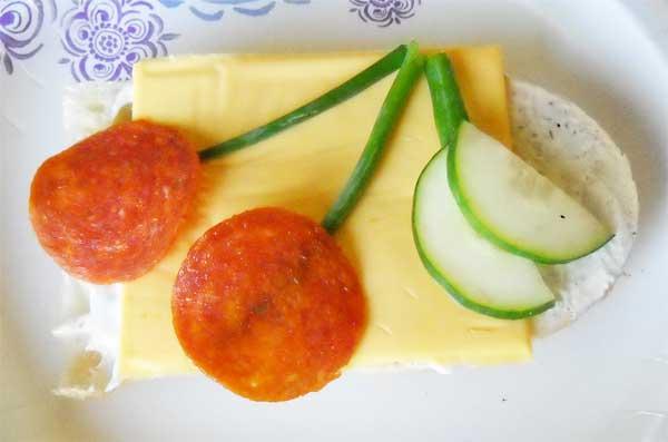 """На 1 бутерброд: хлеб - 1 кусочек; сыр """"Чеддер"""" - 1 пластина; колбаса """" Пепперрони"""" - 2 кружка; лук зеленый - 1 перо; огурец свежий - 1 кружок; майонез или сметана - 1 столовая ложка."""