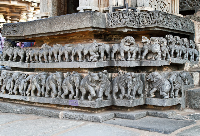 The friezes right from the entrance of the temple, with elephants and lions, below the small model shrines