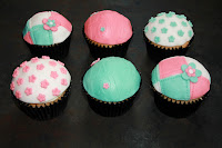6 lemon and passion fruit cupcakes decorated in a pink, white and blue colour scheme