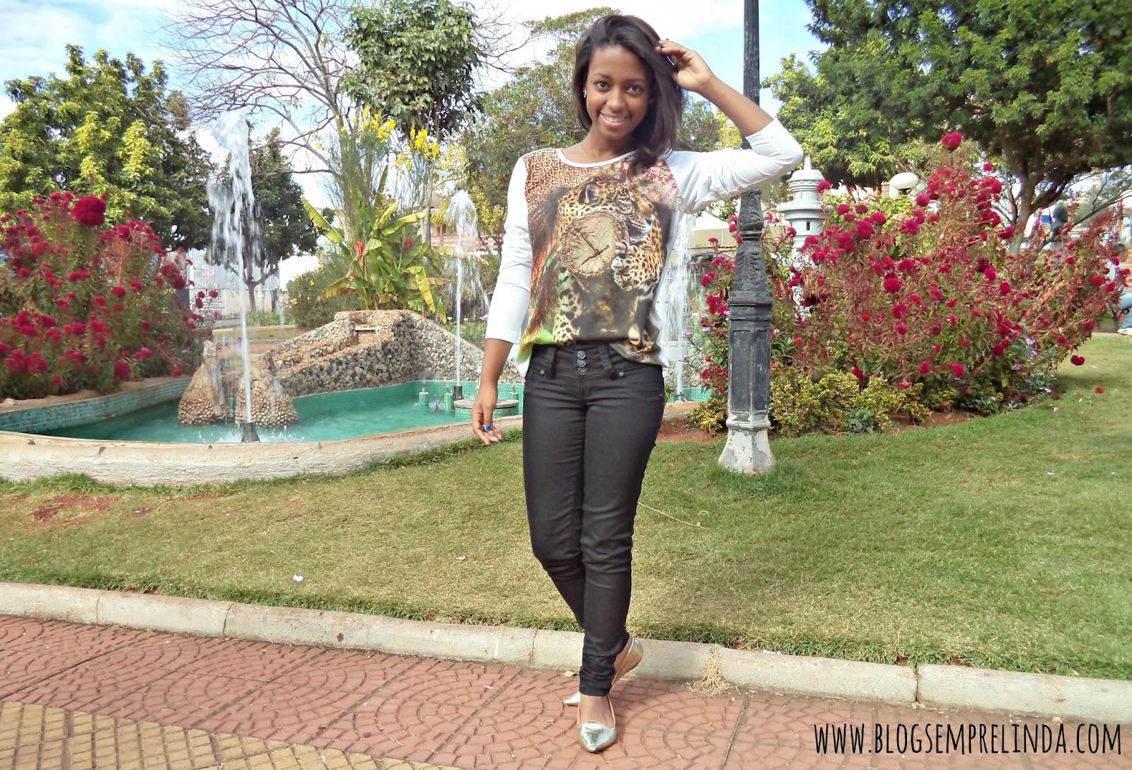 Look composto por calça preta, blusa branca com estampa animal print, com sapatilha dourada. Em uma praça florida.