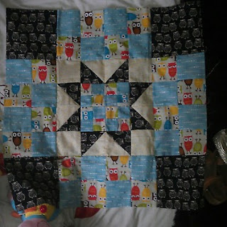 A patchwork mini quilt handmade with an owl theme