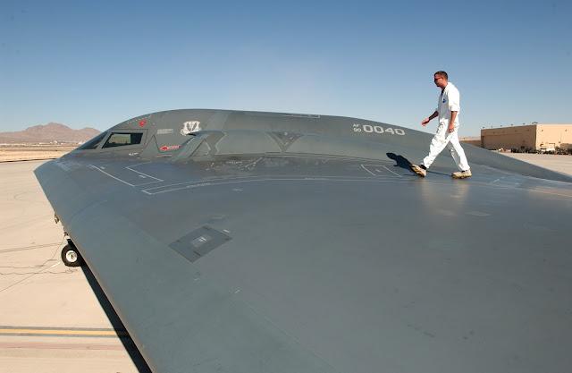 Tech. Sgt. Kevin Ponton examines the wing surface of a B-2 Spirit Bomber