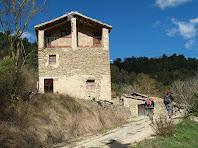 La façana de migdia de La Vall amb un porxo a la planta sota la teulada