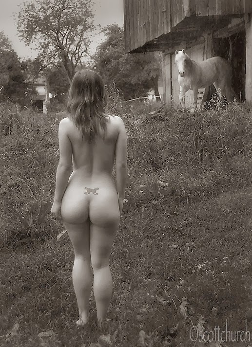 Sara 25 with horse, nude model in a field near a horse stable.