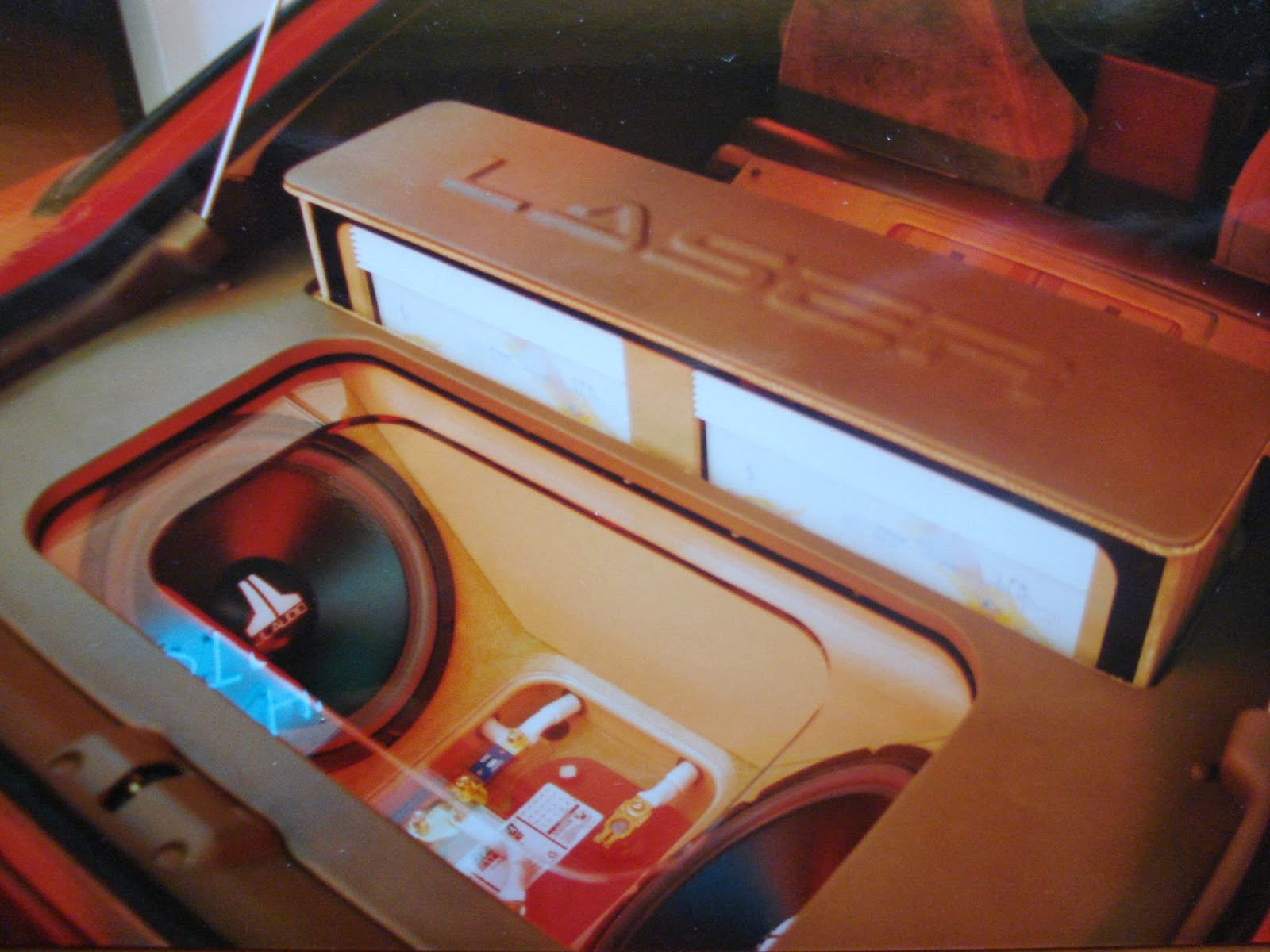 Photo image of the rear hatch area showing the woofer box, the battery rack and the amplifier rack being motorized up in Charles Barbosa's Red Laser as it stood during the winter storage at the end of 1995 and beginning of 1996.