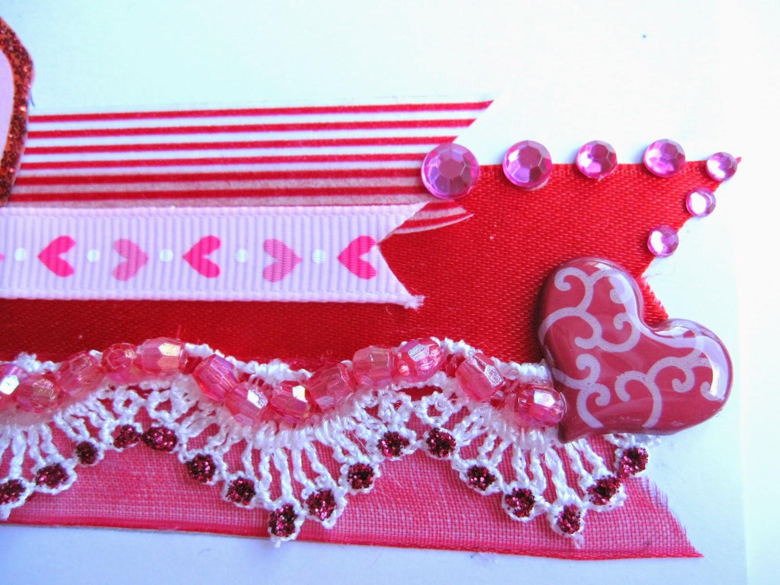detalle tarjeta scrapbooking San Valentín con superposición en rojo y rosa de cintas, washi tape, encaje, corazón brad con glossy accents, diamantes autoadhesivos y cuentas 3D