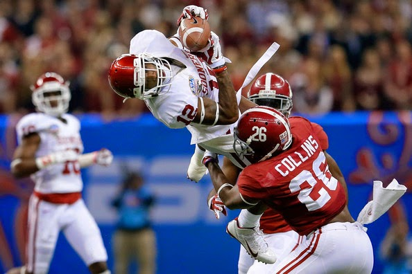 Derrick Woods #12 of the Oklahoma Sooners makes a catch over Landon Collins #26 of the Alabama Crimson Tide during the Allstate Sugar Bowl at the Mercedes-Benz Superdome on January 2, 2014 in New Orleans, Louisiana.