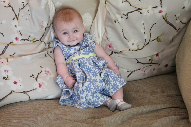 baby girl wearing white and blue floral dress with yellow waist band
