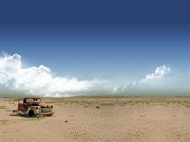 desert landscape with a abandoned car and a bit of vegetation