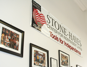 Photos and a banner are displayed on the wall in the Stone-Hayes office