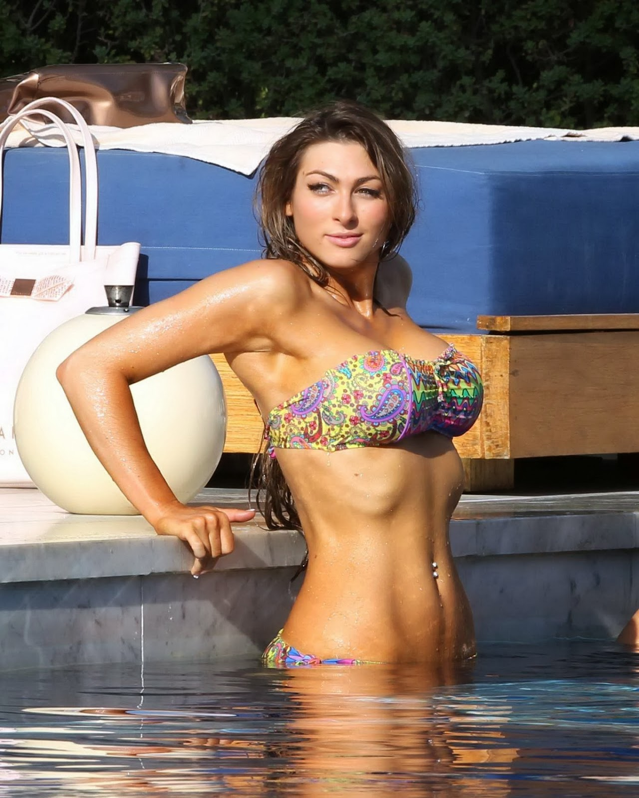 Luisa Zissman showing off her remarkable assets in tube colorful bikini at a pool in Spain