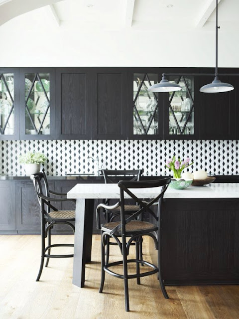 kitchen with dark wood cabinets, island with marble counter top, wood floors, pendant lights and a white black splash with black diamonds on it.