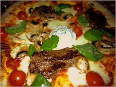 pizza topped with steak, creme fraiche, tomatoes, basil, mushrooms and cheese