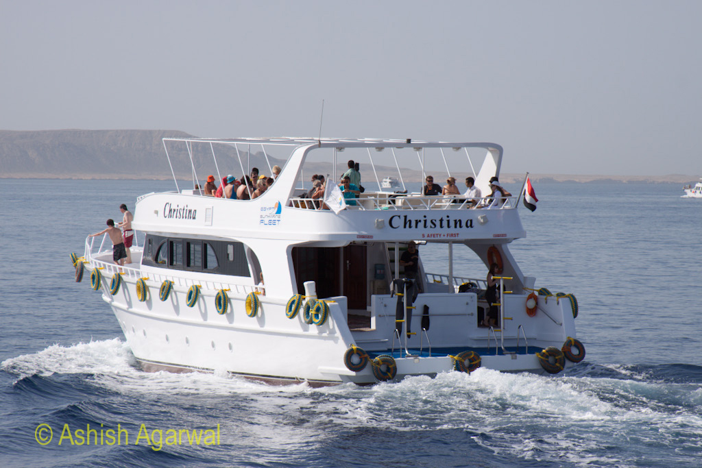 Small ship loaded with tourists heading off towards the coral formations in the Red Sea off Sharm el Sheikh