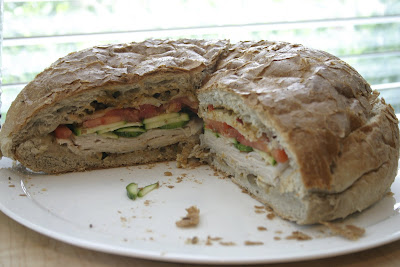layers of turkey and vegetables on a bun