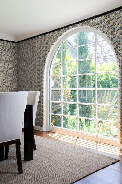 Close up of the arched window, graphic wallpaper and sleek black crown molding