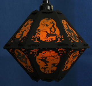 Witches on rockets in outer space imagery of orange and black classic style paper pendant latnern by Bindlegrim