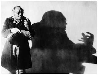 Imagen con un fotograma de la película El gabinete del doctor Caligari que muestra al doctor Caligari proyectando una siniestra sombra de la expresión de sus manos