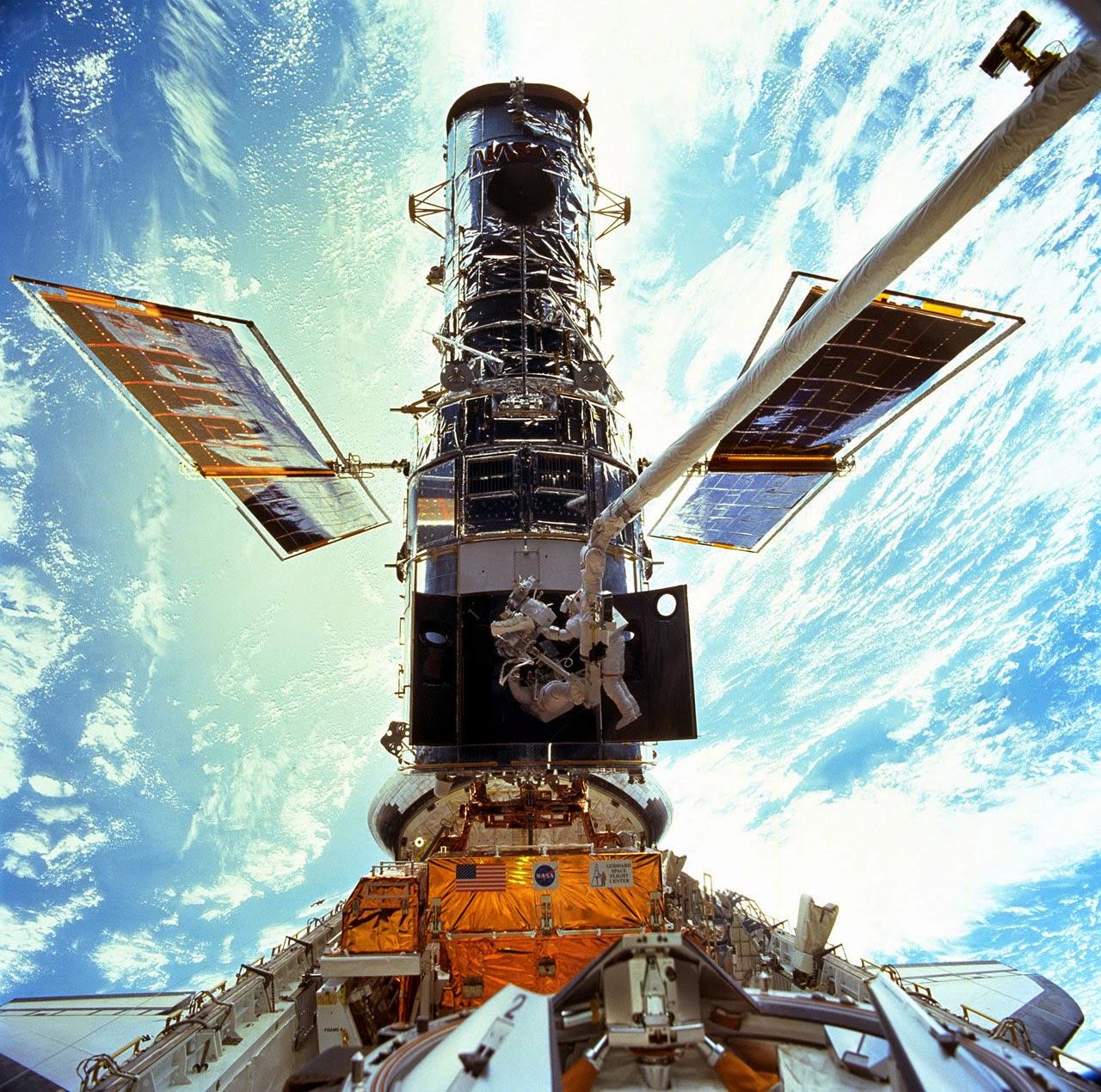 Высоко над Землёй астронавты занимаются ремонтом телескопа Хаббл, пристыкованного к космическому челоноку (в нижней части изображения)