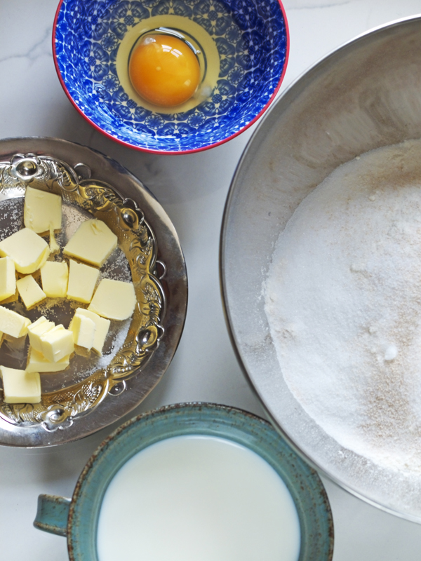 Mise en place egg, butter, flour, yeast, milk for yeast dough crescents.