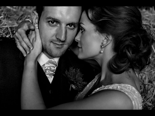 bride in passionate embrace with her groom wearing a lace bridal gown and loose curled hair
