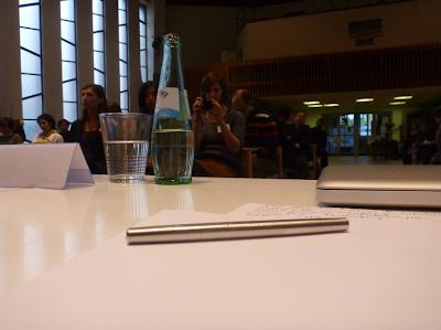 Die Subjektive der Dolmetscherin: Vor mir Papier, Stift, Computer, die Redner haben ihre Schilder. Und vom Publikum sehe ich nicht viel, nur das Licht hinter den Fenstern ...