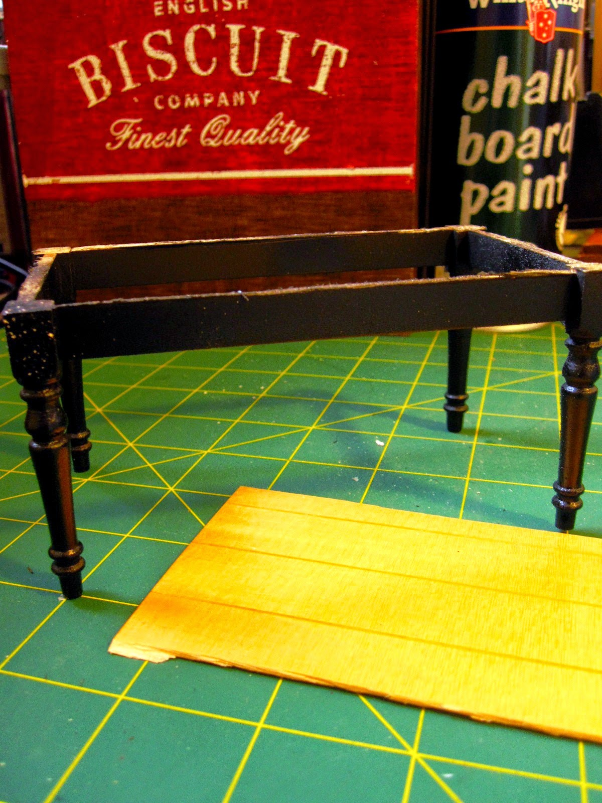 Miniature dining table leg assembly, painted black, sitting on a cutting mat with a spray can of chalkboard paint.