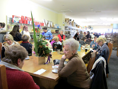 A group of customers chatting around the worktable in the new Fairy Meadow Miniatures shop.