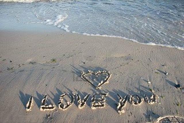Un corazón más un te amo en la arena