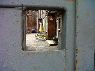 View of a courtyard with table and yellow umbrella, seen through a square hole in a steel door