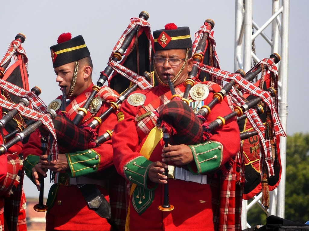 Army band in uniform playing bagpipes