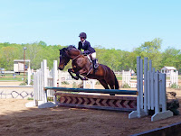 A young rider and her horse sail over a jump at Mystic Valley Hunt Club in Mystic, CT